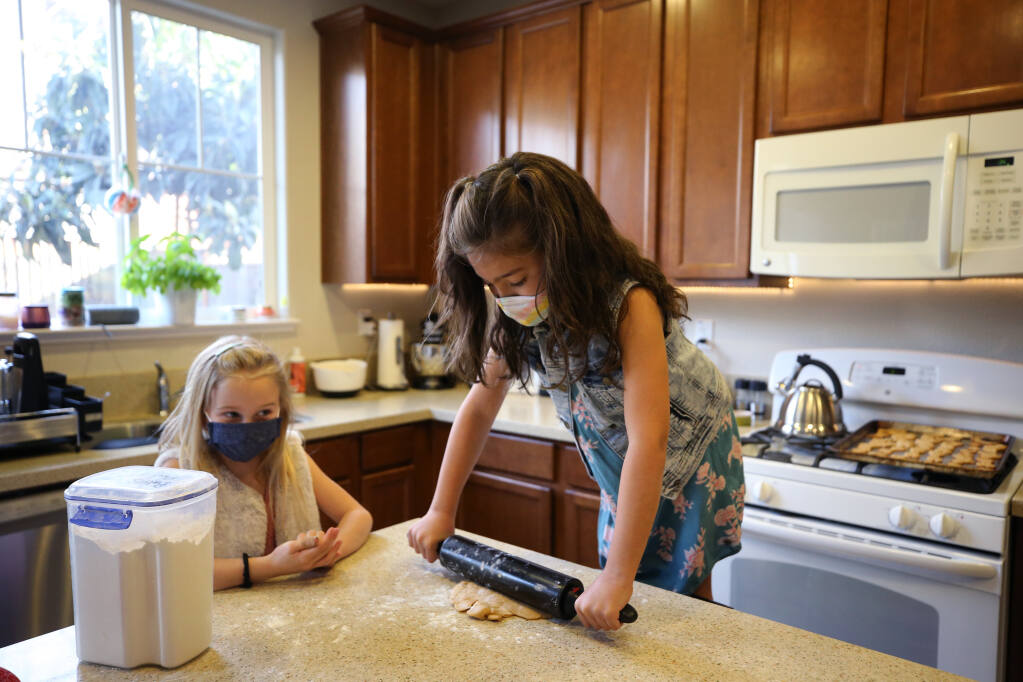 Priya Leach, 7, stands on a chair as she rolls out the dough to make homemade dog treats that she and her friend, Emmie Lenz, 8, are baking and selling as a fundraiser for North Bay Animal Services. Photo taken at the Leach home in Petaluma on Wednesday, March 3, 2021. (Beth Schlanker / The Press Democrat)