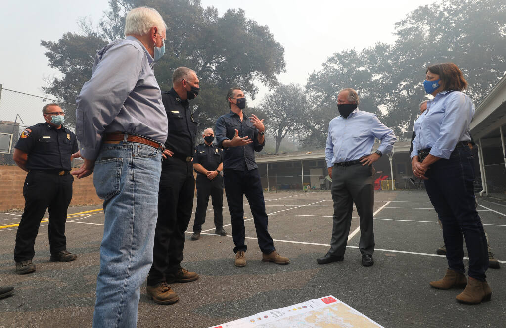 Rep. Mike Thompson, Cal Fire Director Thom Porter, Gov. Gavin Newsom, Sen. Bill Dodd and Assemblywoman Cecilia Aguiar-Curry discuss the Glass fire at Foothills Elementary School near St. Helena on Thursday, Oct. 1, 2020. (Christopher Chung / The Press Democrat)