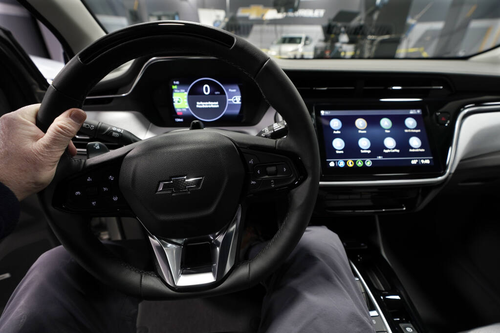 A driver handles the wheel of a 2022 Bolt EUV on Feb. 11, 2021, in Milford, Michigan. Automakers are rolling out multiple new electric vehicle models as the auto industry responds to stricter pollution regulations worldwide and calls to reduce emissions to fight climate change.  (Carlos Osorio / Associated Press)