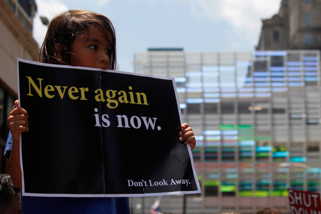 A young girl holds up a protest sign to demand the closure of detention camps at the U.S.-Mexico border. Philadelphia, PA / USA - July 12, 2019.