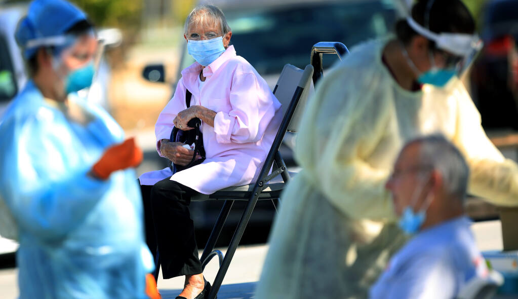 Lois Dresnik watches as her husband George, of Windsor, prepares to receive a COVID-19 nose swab from Sonoma County Public Health nurse Devin Andrews, Tuesday, Oct. 20, 2020 at Andy's Unity Park in Santa Rosa.  (Kent Porter / The Press Democrat) 2020