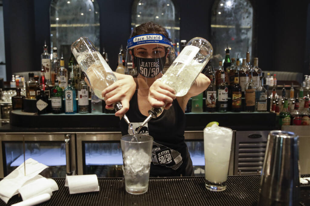 FILE - In this July 1, 2020, file photo, a bartender mixes a drink while wearing a mask and face shield at Slater's 50/50 in Santa Clarita, Calif.  (AP Photo/Marcio Jose Sanchez, File)