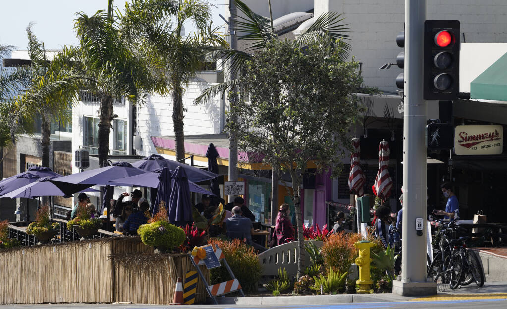 """Patrons pick up their food to go orders at Simmzy's restaurant counter, right, before sitting to consume their meals at a """"Public Parklet"""" outdoors area, seen left, in Manhattan Beach, Calif., Thursday, Dec. 10, 2020. (AP Photo/Damian Dovarganes)"""