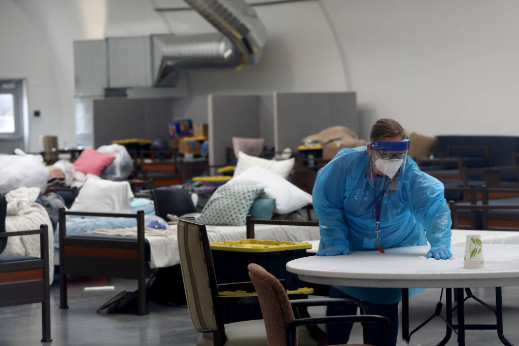 Devon Stoddard, a program manager with Catholic Charities, cleans inside a living space used recently to quarantine residents with COVID-19 at the Sam Jones Hall in Santa Rosa, Calif., on Monday, July 26, 2021.(Beth Schlanker/The Press Democrat)