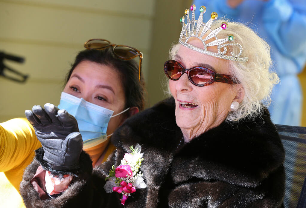 Edie Ceccarelli waves at people driving by wishing her a Happy 113th Birthday in Willits on Friday, February 5, 2021.  (Christopher Chung/ The Press Democrat)