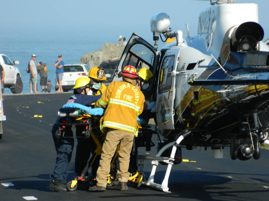 A man who was bitten by a shark while surfing off Salmon Creek Beach in Sonoma County, Calif. is loaded into a helicopter before he is airlifted to a hospital on Sunday, Oct. 3, 2021. (Pat Paterson)