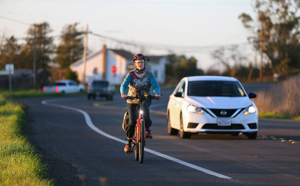 Eris Weaver, executive director of the Sonoma County Bicycle Coalition, commutes home on her e-bike after work, along Petaluma Hill Road, in Santa Rosa on Wednesday, Feb. 10, 2021. (Christopher Chung / The Press Democrat)
