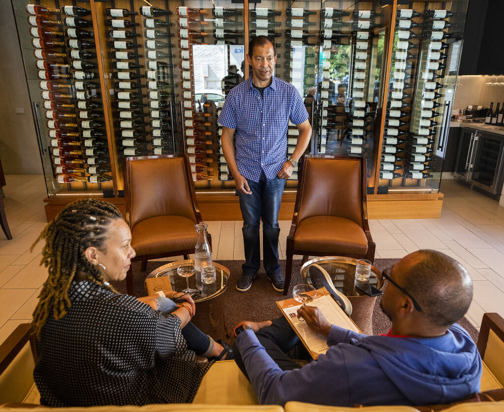 Lloyd Davis, owner of the Corner 103 tasting room in Sonoma, talks with guests Sheray, left, and Kirk Law of Cupertino about his wines on Friday, September 17, 2021. (Photo by John Burgess/The Press Democrat)
