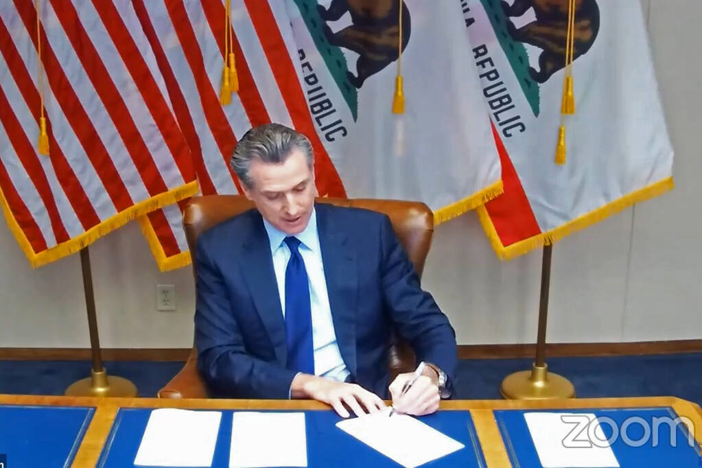 """In this image taken during a video broadcast via Zoom, California Gov. Gavin Newsom signs a law on Friday, Sept. 25, 2020, in Sacramento, Calif.,  that for the first time defines """"medical necessity,"""" a move aimed at requiring private health insurance plans to pay for more mental health and drug addiction treatments.  (Zoom via AP)"""