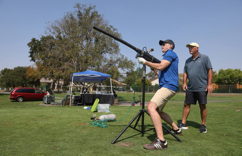 Andrew Grossman, left, fires his golf ball out of a ball cannon, under the supervision of Jeff Siegel, to raise money for Dogwood Animal Rescue, during the Coldwell Banker Golf Tournament hosted by Guaranteed Rate Infinity at the Windsor Golf Club on Friday, September 3, 2021.  (Christopher Chung/ The Press Democrat)