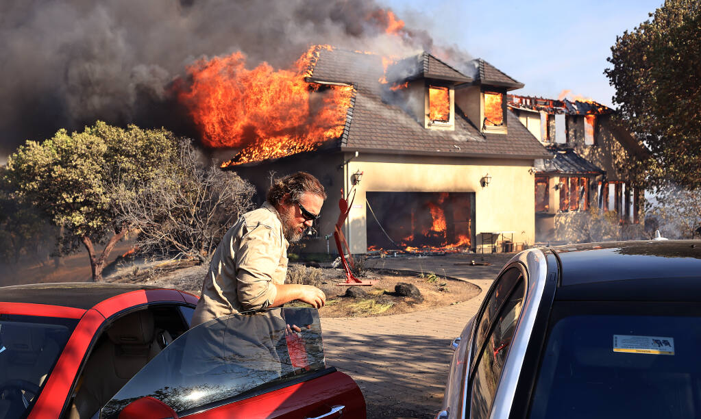 Joe Kikuchi  of Pacific Gas and Electric moves cars to safety as a house in Marina Estates above Lake Mendocino on the Hopkins fire burns, Sunday, Sept. 12, 2021 near Calpella.  (Kent Porter / The Press Democrat) 2021