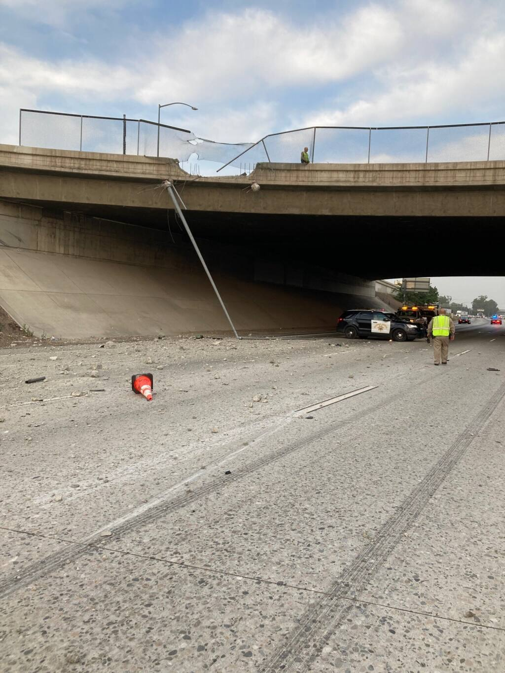 This photo provided by the California Highway Patrol Rancho Cucamonga shows a damaged concrete barrier on a Southern California overpass where a pickup truck crashed through onto the road below on Tuesday, June 29, 2021 in Fontana, Calif. The pickup truck driver was killed when he crashed through the fencing and concrete barrier of the overpass and flew over the edge and smashed onto the freeway below early Tuesday, authorities said. The man, whose name has not been released, was driving his 2005 Ford pickup around 4:10 a.m. at a high speed on Interstate 10 in Fontana, the California Highway Patrol said in a news release. (CHP Rancho Cucamonga via AP)