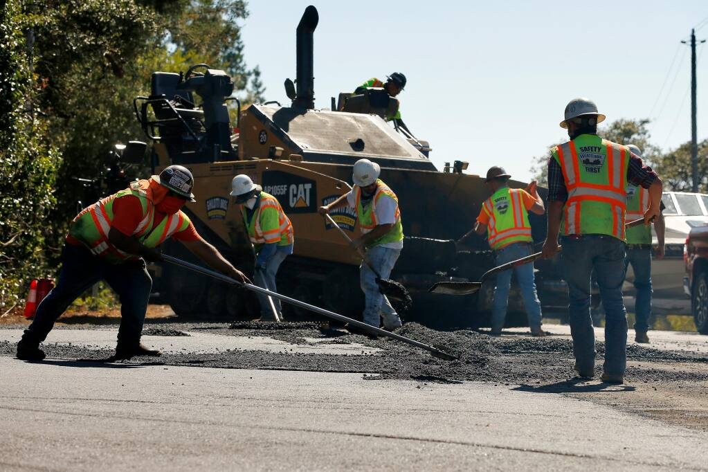Workers with Ghilotti Bros. Contractors spread asphalt as they repave Barnett Valley Road at Bodega Highway outside Sebastopol on Wednesday, July 29, 2020. (Alvin Jornada / The Press Democrat)