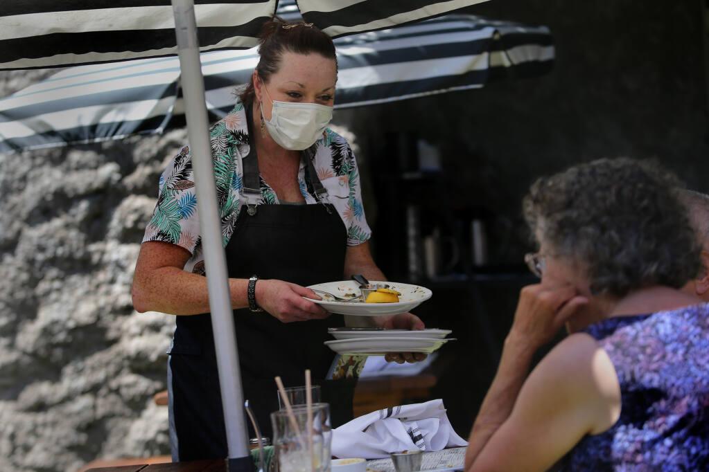Waitress Shannon Dolan checks in on a table at Grossman's Noshery in Santa Rosa on Monday, Aug. 9, 2021. (Beth Schlanker/The Press Democrat)