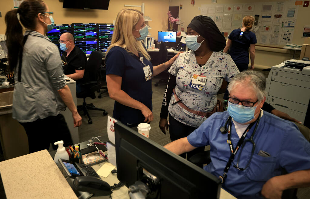 Registered nurses Sara Fisher, middle left, and Alicia Prime greet one another as registered nurse Eric Cullen prepares paperwork. Tuesday, June 22, 2021, in what was once a COVID-19-dedicated ICU ward at Sutter Santa Rosa Regional Hospital.  (Kent Porter / The Press Democrat) 2021