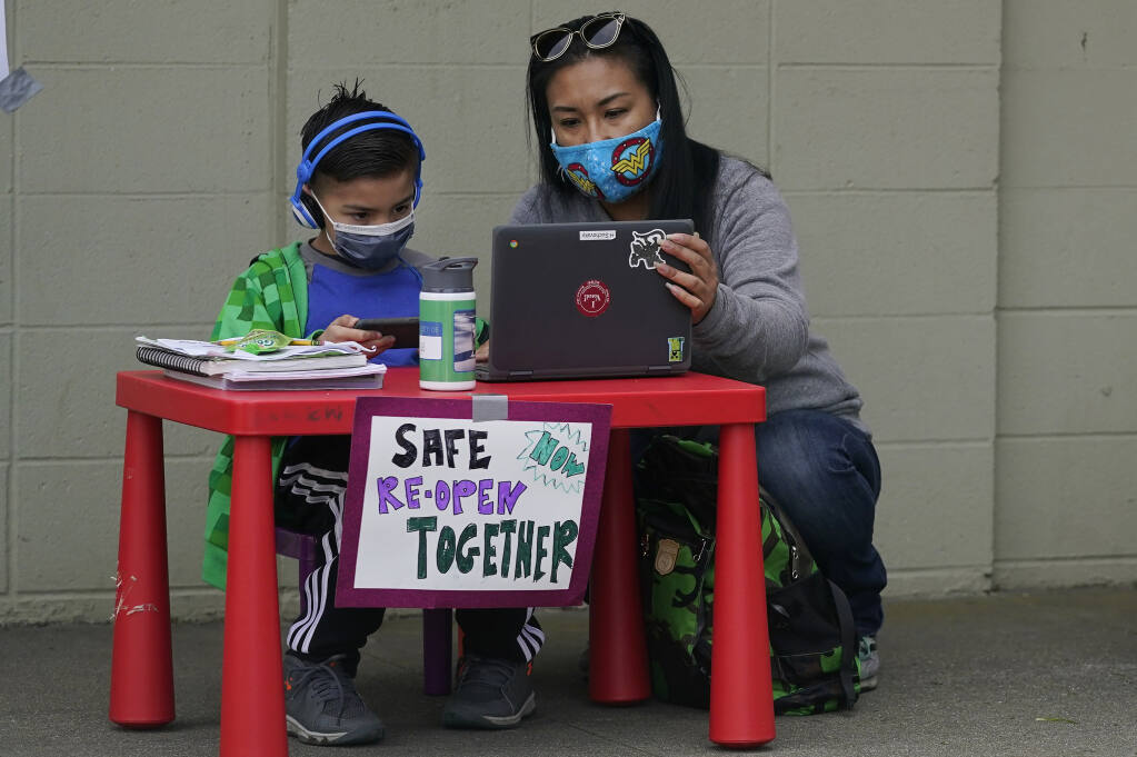 FILE - In this Thursday, Feb. 18, 2021, file photo, Maya Peralta, right, sits with her son, Clarendon Alternative Elementary School second-grader H Suchovsky, as students and parents attend distance learning Zoom classes at Midtown Terrace Playground in San Francisco. School officials plan to reopen classrooms for some of the youngest students beginning April 12 under a tentative deal reached with the teachers union, according to a newspaper report. The agreement was announced late Friday, March 5, 2021, after months of debate over how and when kids would return to in-person instruction as coronavirus cases and hospitalizations decline statewide. (AP Photo/Jeff Chiu, File)