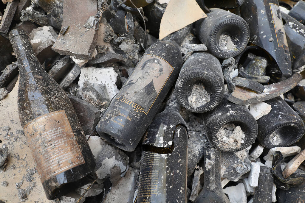 A bottle of Courage lays among the rubble of the Fairwinds Estate Winery, which was destroyed by the Glass  fire, in St. Helena on Tuesday, Sept. 29, 2020.  (Christopher Chung / The Press Democrat)
