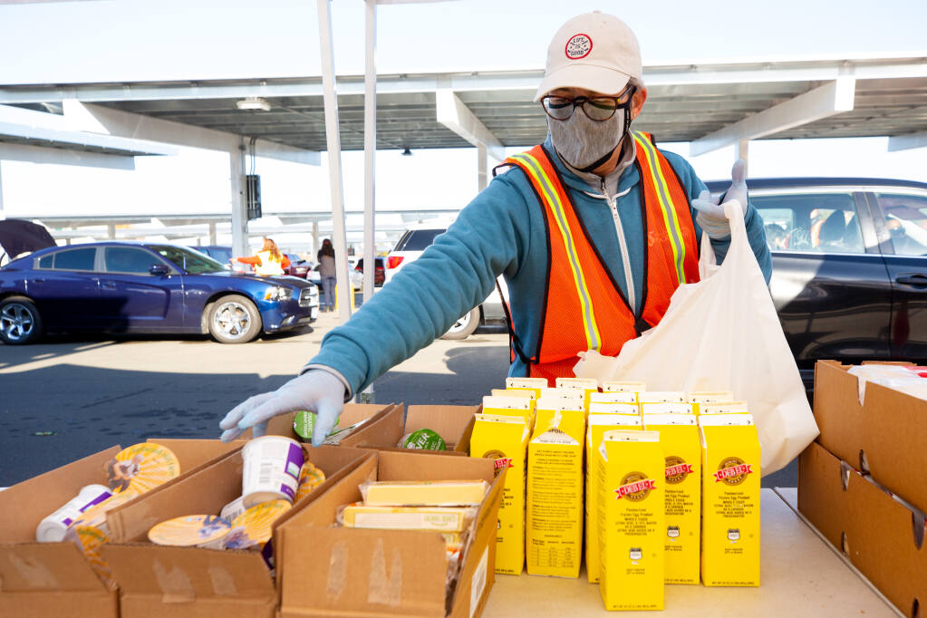 Volunteer Mary Seggerman bags dairy products for recipients during a Redwood Empire Food Bank food distribution at Kaiser Permanente in Santa Rosa on Saturday, Nov. 21, 2020. (Alvin A.H. Jornada / The Press Democrat)