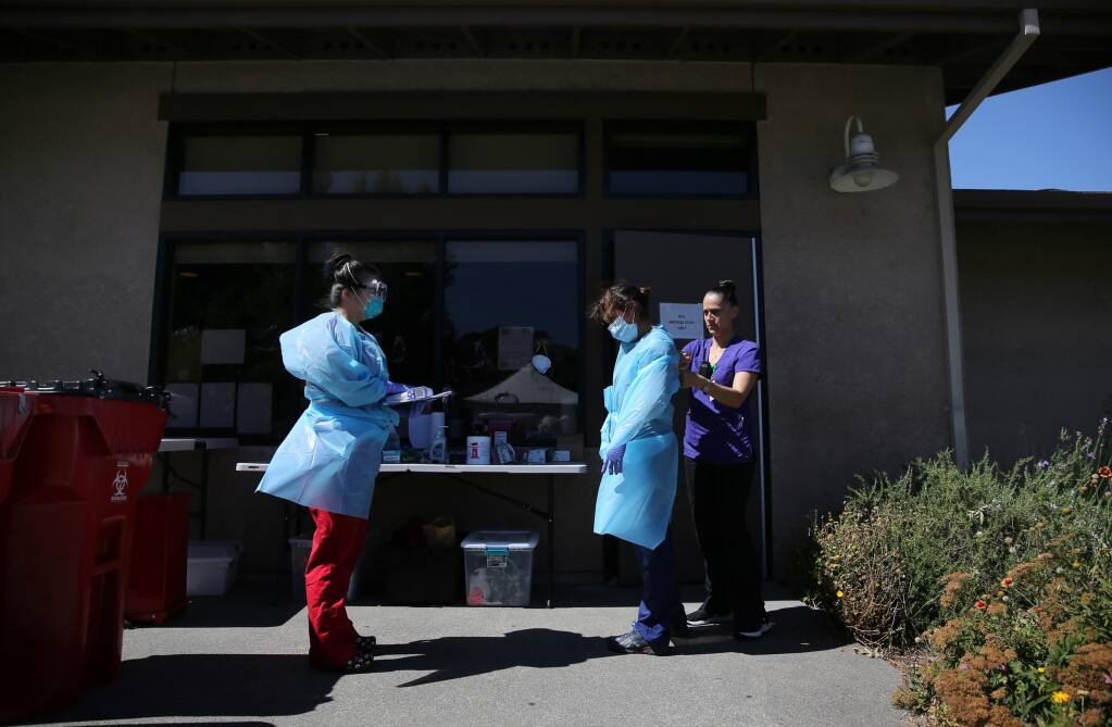 (From left) Registered nurses Sandra Castano and Nicole Garcia suit up with help from Rachael Lopez as they prepare to walk through the Sauvignon Village student housing complex and check on some of the temporary residents quarantining from COVID-19 on the Sonoma State University campus in Rohnert Park, California, on Sunday, July 5, 2020. (Beth Schlanker/The Press Democrat)