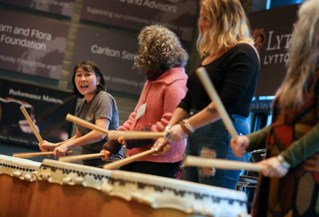 Meg Mizutani, teaching artist and Taiko drummer, left, teaches volunteers how to drum during a demonstration at the Sonoma County Arts Education Framework breakfast event at the Luther Burbank Center for the Arts in Santa Rosa on Thursday, Dec. 12, 2019. (Christopher Chung/ The Press Democrat)